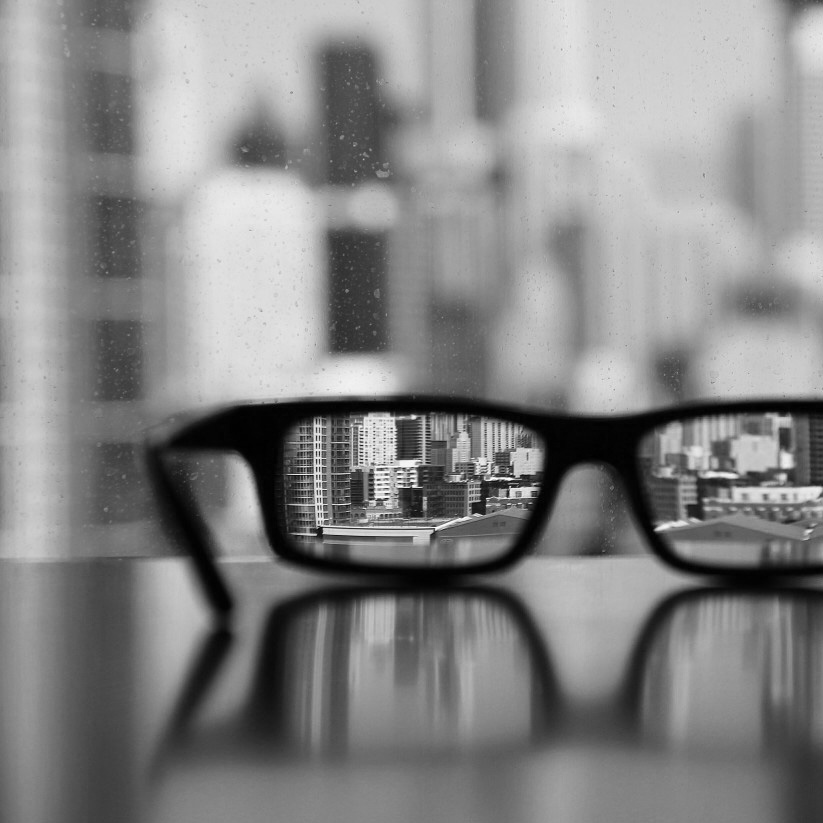 Eyeglasses laying on a desk with a skyscraper backdrop